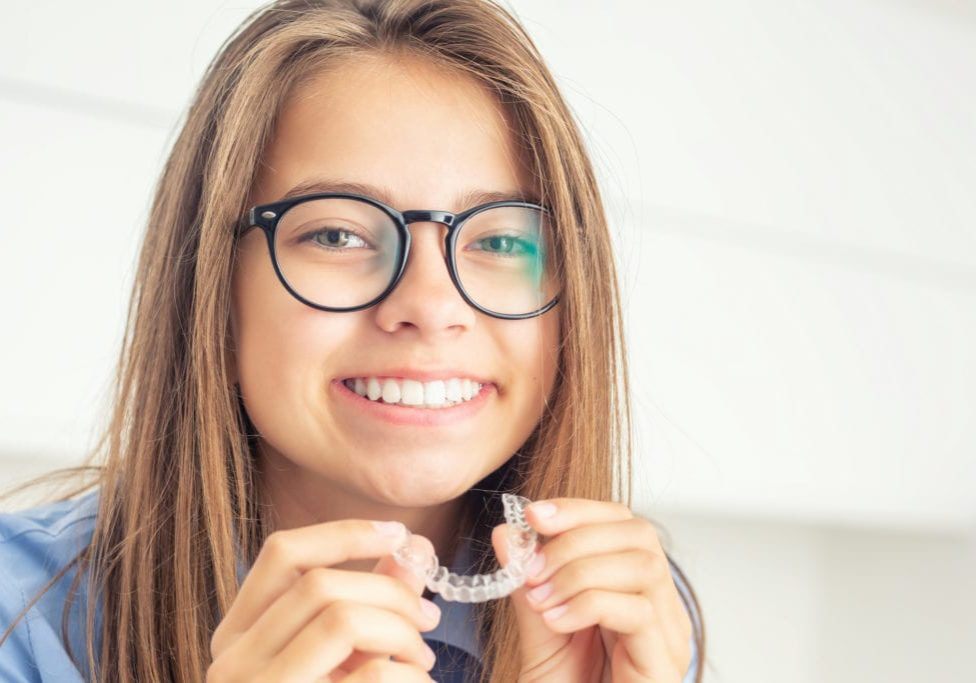 Young girl with dental invisible braces.